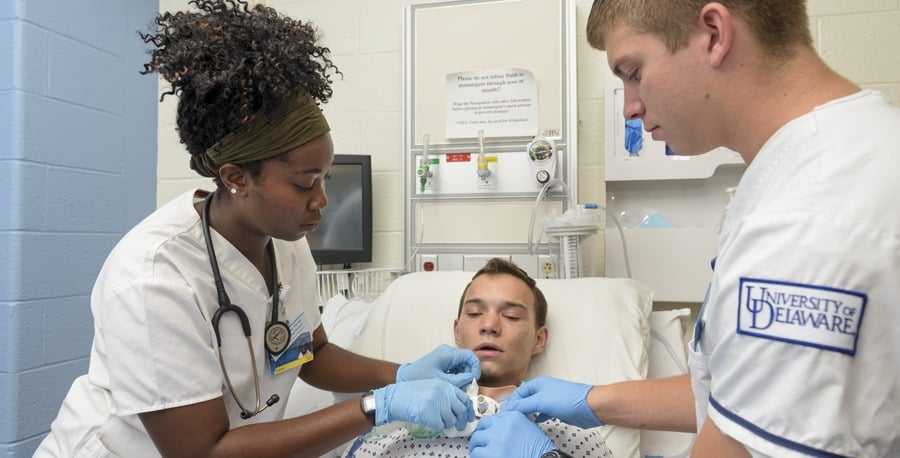 """Nursing students Jerelene Thorpe (left) and Cory Haaf (right) were among the first to practice tracheostomy care in a unique way in 2016—using the lifelike Avtrach device, worn by volunteer """"patient"""" Robert Tilley (center)."""