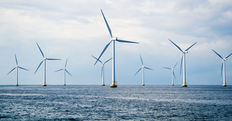 Nine wind turbines at sea. Windmills in blue ocean with a clouded blue sky. iStock